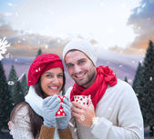 Winter couple holding mugs — Стоковое фото