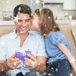 Girl kissing father holding gift box on sofa — Stock Photo #53900399