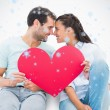 Couple sitting holding red heart — Stock Photo #53900549