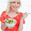 Young smiling woman eating a fresh salad — Stock Photo #53901173