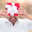 Festive man holding christmas gift — Stock Photo #53901845