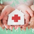 Couple holding paper house with red cross in hands — Stock Photo #53902511