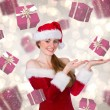 Composite image of pretty girl in santa costume holding hand out — Stock Photo #53902571