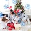 Family opening Christmas presents — Stock Photo #53902923