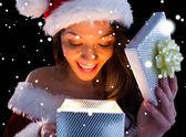 Brunette in santa outfit opening gift — ストック写真