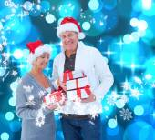 Mature couple holding christmas gifts — Foto de Stock