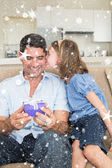 Girl kissing father holding gift box on sofa — Stock Photo