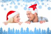 Festive couple smiling from behind poster — Stock Photo