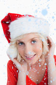 Blonde woman putting on Santa hat — ストック写真