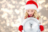 Composite image of happy festive blonde with clock — Stock Photo