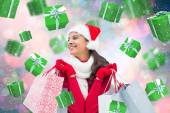 Composite image of festive brunette holding shopping bags — ストック写真