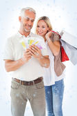 Happy couple holding shopping bags and cash — Stockfoto