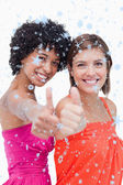 Smiling teenage girls proudly showing their thumbs up — Stock Photo