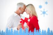 Smiling couple passing a wrapped gift — Stock Photo