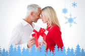 Smiling couple passing a wrapped gift — Foto de Stock