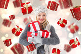 Composite image of happy blonde with gifts — Stock Photo