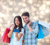 Couple with shopping bags and credit card — Stock Photo