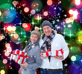 Mature couple holding christmas gifts — Stockfoto