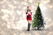 Pretty girl in santa costume holding gift box — Stock Photo