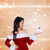 Girl in santa outfit holding gift — Photo