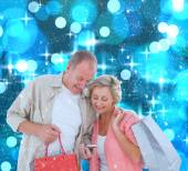 Couple with shopping bags and smartphone — Stock Photo
