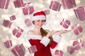 Composite image of pretty girl in santa costume holding hand out — Stock Photo