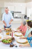 Senior man serving meal to family — Stock Photo