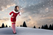 Girl in santa outfit blowing — Stock Photo