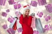 Composite image of happy festive blonde with shopping bags — ストック写真