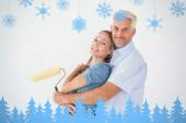 Happy couple hugging and holding paint roller — Stock Photo