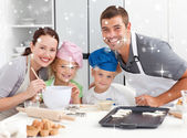 Joyful family cooking littles cakes — Stock Photo