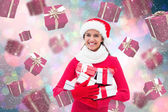 Composite image of festive brunette holding gifts — Stockfoto