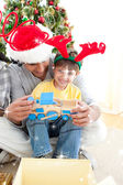 Father and son playing with present — Stock Photo