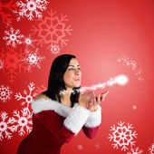 Girl in santa outfit blowing — 图库照片