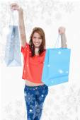 Teenage girl smiling and raising her shopping bags — Stock Photo