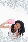 Woman looking inside her piggy bank — Stockfoto