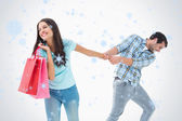 Attractive young man pulling his shopaholic girlfriend — Foto de Stock