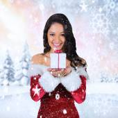 Girl in santa outfit holding gift — Stock Photo