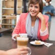 Pretty brunette enjoying her latte with a friend — Stock Photo