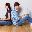 Young couple sitting on floor using laptop — Stock Photo #53914409