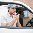 Delivery driver talking on walkie talkie by his van — Stock Photo #53915157