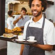 Handsome waiter smiling at camera holding tray — Stock Photo #53915443