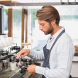 Handsome barista making a cup of coffee — Stock Photo #53916397