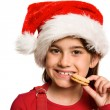 Festive little girl eating cookie — Stock Photo #53917643