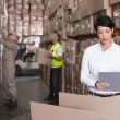 Warehouse manager writing on clipboard — Stock Photo #53917869