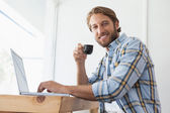 Casual man using laptop drinking espresso — Stock Photo
