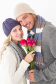 Attractive couple in warm clothing holding flowers — Stockfoto