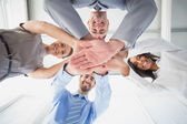 Four workers stacking hands together — Stock Photo
