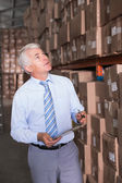 Warehouse manager checking his inventory — Stockfoto