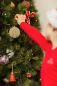 Festive little girl hanging a christmas decoration — Stock Photo